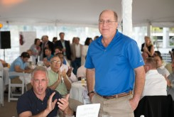 Man standing with his hands in his pockets while attendees around him applaud at the 2013 Howard F. Treiber Memorial Golf Outing