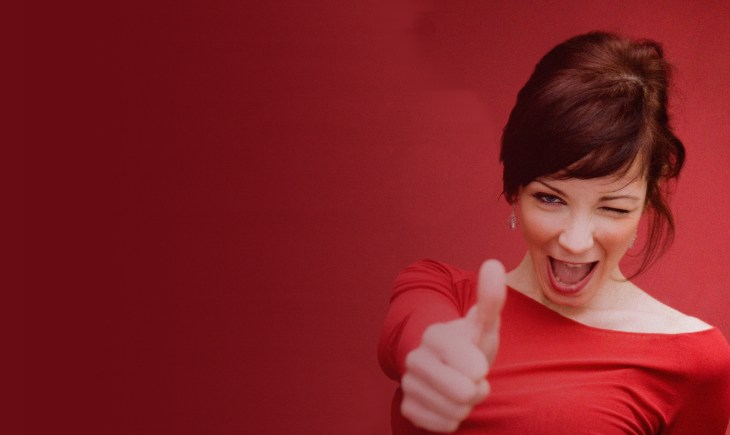 Lady dressed in red giving a thumbs up