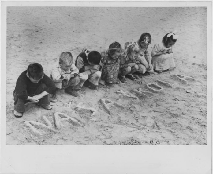 """Croatian children wrote the words for """"our school"""" in the sand of the Tolumbat camp in 1945."""