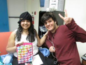 two adolescent students smiling while listening to music