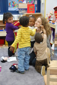 Teacher kneeling while young students surround her