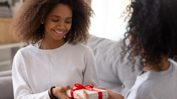 A mother giving one of the best gifts for teenagers on her birthday.