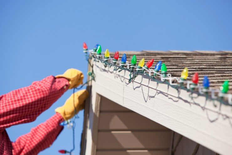 An unrecognizable person hanging Christmas lights.