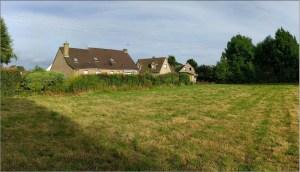terrain vague à bâtir avec maison en arrière plan