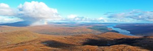 Photo of a panoramic autumnal view across Sutherland from Meallan a' Chuail above Loch Merkland to Ben Klibreck, behind the shower, and Loch Shin to the right