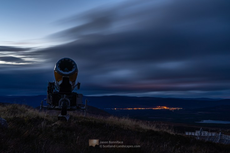 Photo of a Cairngorm Mountain ski centre snow cannon in place ready for winter. I came across this one with the bright lights of Aviemore behind during descent at dusk.