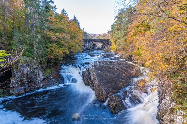 Photo of the River Moriston flowing east to Loch Ness through Invermoriston, the current and old bridges upstream