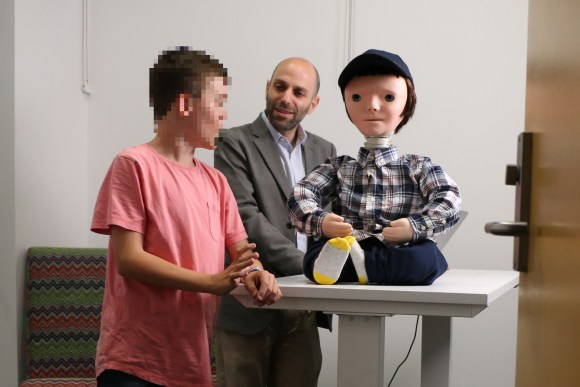 A boy and male researcher stand beside the Kaspar robot. The boy's face is pixelated for privacy reasons.