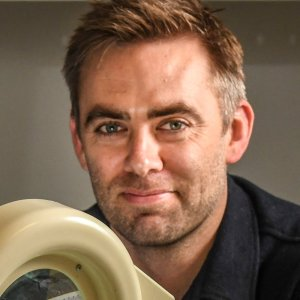 A headshot of Dr Scott Brown during a promotional photoshoot with the Kaspar robot at UNSW Art & Design Creative Robotics Lab.