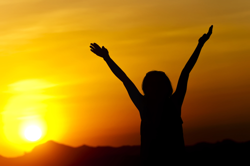 Woman stretches her arms to sky and sun
