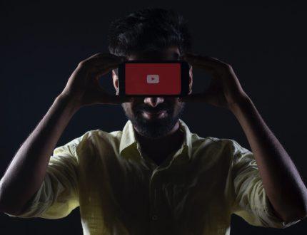 man holding screen displaying YouTube logo