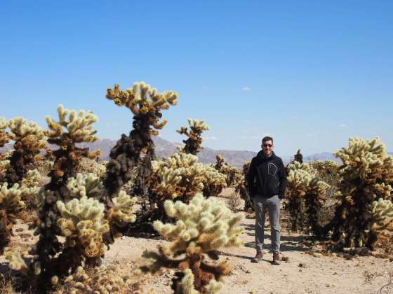 Scott Mallinson standing in a southern California desert surrounded by cacti
