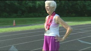 elderly lady wearing a race walking medal around her neck.
