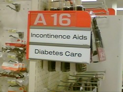 "Store Isle sign that says ""Incontinence Aids & Diabetes Supplies"""