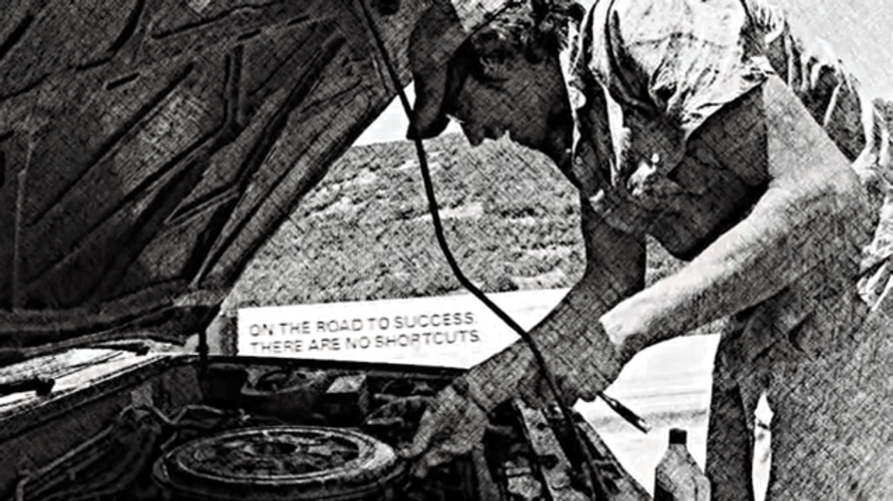 "Black and white image of Steve under the hood of his broken down car, while a semi zooms by in the other direction with a sign that says ""on the road to success there are no shortcuts."""