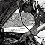 """Black and white image of Steve under the hood of his broken down car, while a semi zooms by in the other direction with a sign that says """"on the road to success there are no shortcuts."""""""