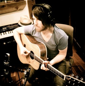 Landon Bailey playing acoustic guitar in the studio