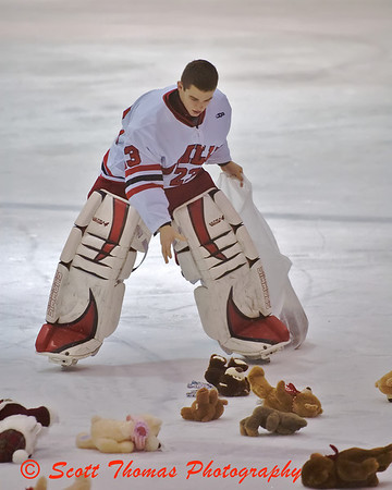 A Baldwinsville player helps to collect Teddy Bears thrown by spectators during the first intermission of the Baldwinsville Varsity Boys Ice Hockey game.  Teddy bears were donated to the Crouse Hospital.