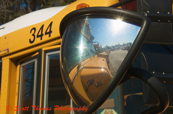 A safety mirror gives a wide angle view of the fleet of parked busses.