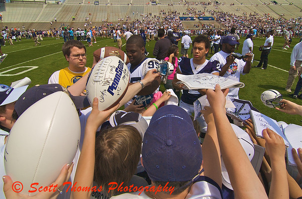 Penn State Football players, Abe Koroma (95, in white) and Evan Royster (22, in blue), autograph footballs, programs, notebooks, miniature helmets, t-shirts, hats, and posters before the annual Blue-White Intrasquad Spring game in Beaver Stadium on the Pennsylvania State University campus, College Park, Pennsylvania.