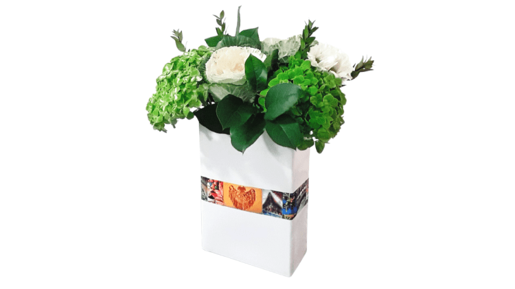 A rectangular white vase decoupaged with cut-outs from an old travel calendar and filled with green & white flowers and green leaves