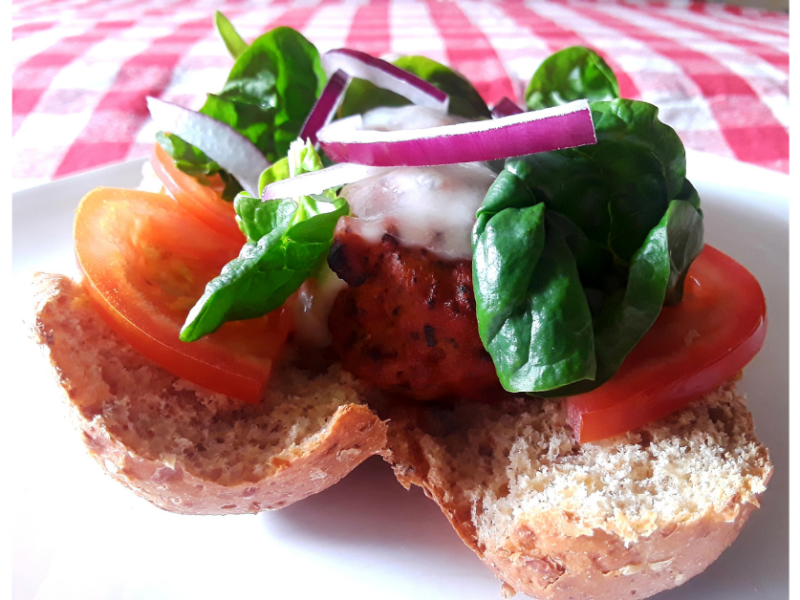 Close up of a meatball sandwich with meatballs on a bun with sliced tomato, spinach, and red onion