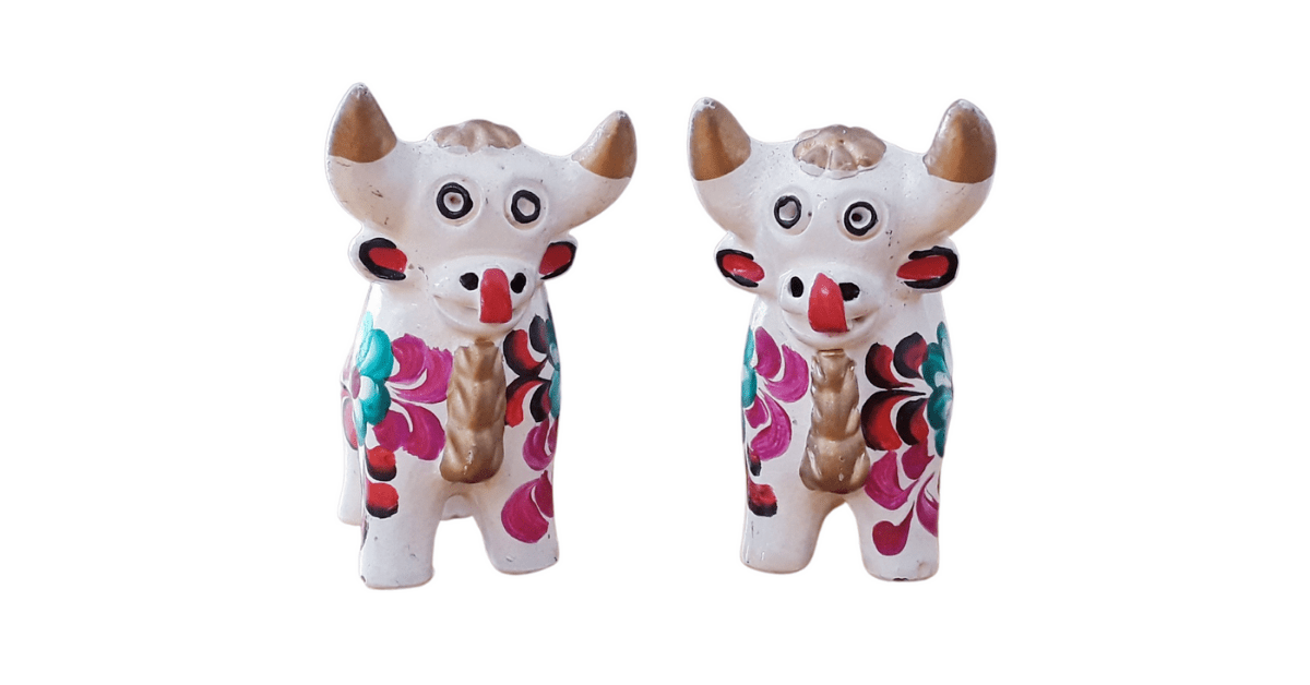 Two white ceramic bulls with gold horns, a gold crown, and hot pink, orange, and green flowers