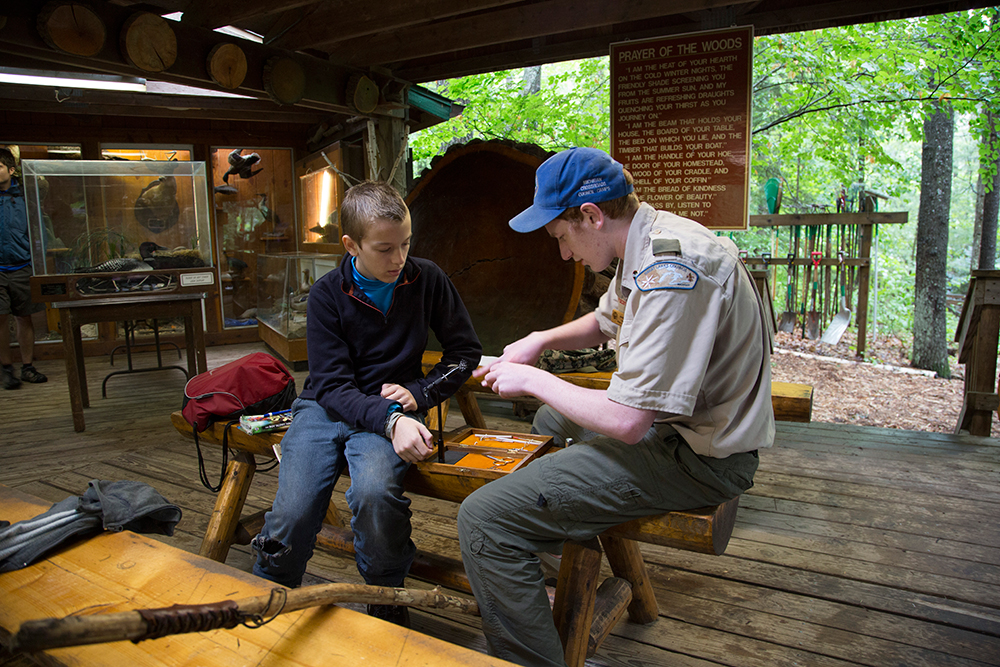 Staffer Jared Wolfe teaches Alex Duerksen of Troop 164 from Okemos, Mich., how to tie a fishing fly.