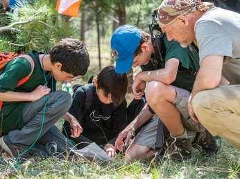 Scouts and Les Stroud look over a map.