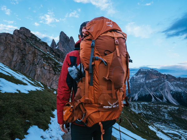 Man wearing a large orange backpack in the mountains
