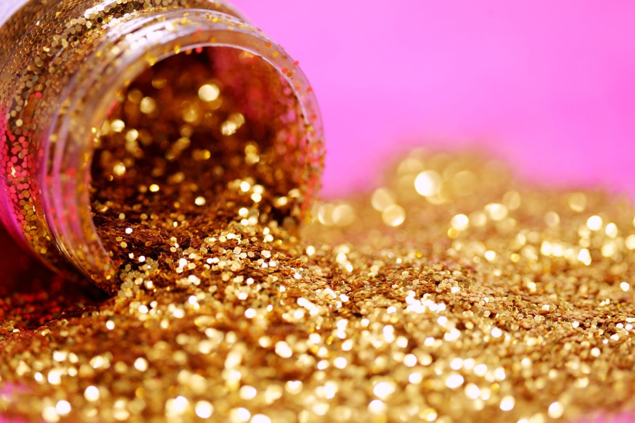 Macro shot of gold glitter spilled on a pink background
