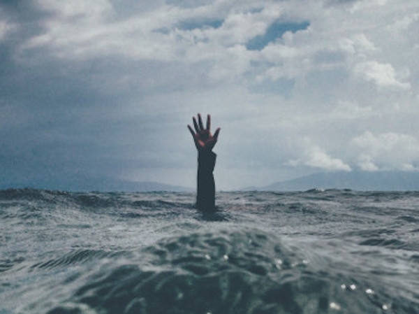 Drowning hand reaching up from the ocean