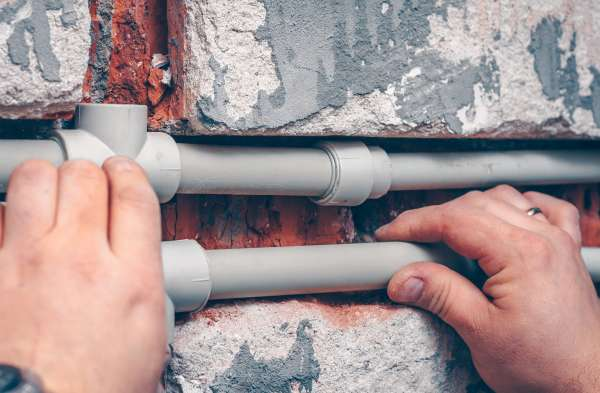 The worker carries out plumbing works in the house, mounts water pipes from polypropylene