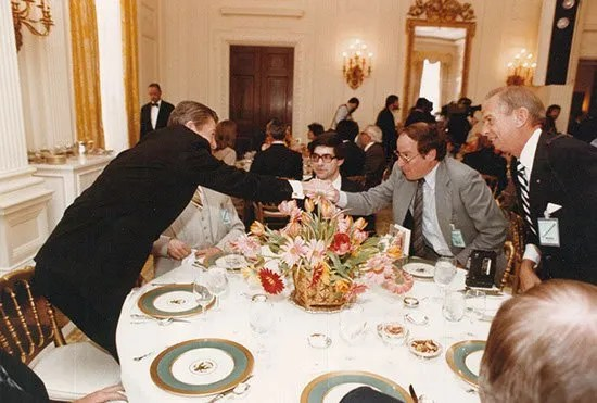 Krell shakes hands with President Reagan at a 1982 luncheon for editors.