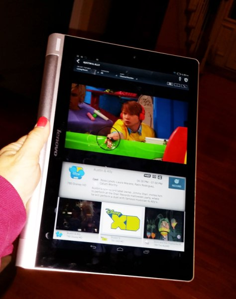 Holding the Yoga Tablet in hold mode to continue watching while handing out candy.
