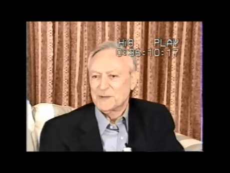 Leonard Levine seated on a couch wearing a collared shirt and dark sport coat.