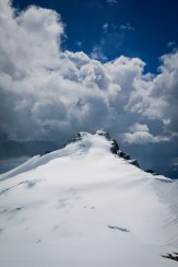 Summit of eleven-thousand-footer Mount Hector with stormclouds enveloping dark blue skies above me…