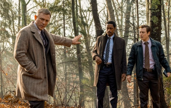 3 men standing in the woods, one with arm outstretched