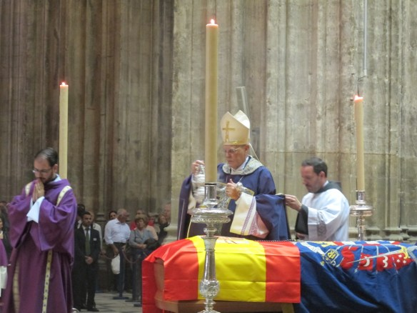 The Archbishop Cardinal of Seville blesses the Duchess, swathed in the flags of Spain, and the Casa de Alba.