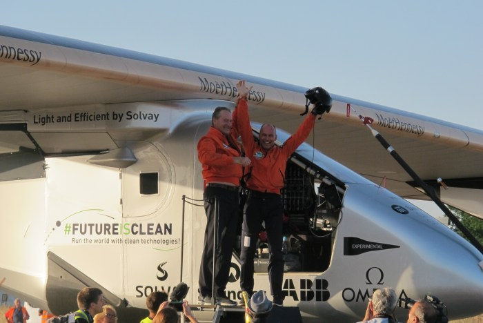 Bertrand Piccard hails the assembled throng as he climbs out of the planes cockpit after his three-day flight.