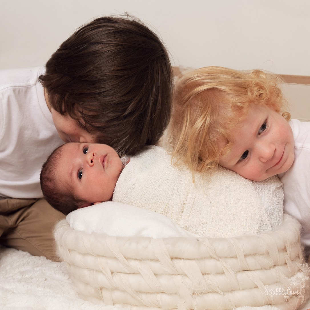Wollongong In Home Newborn Photographer. Newborn baby with two big brothers snuggling in.