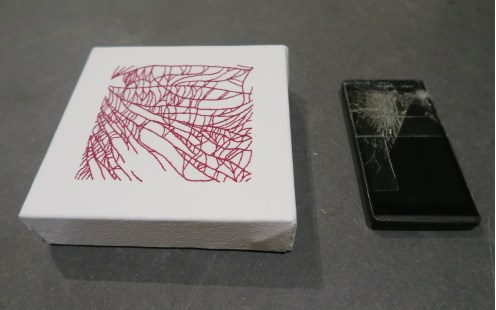 sewn replica of a smashed mobile phone