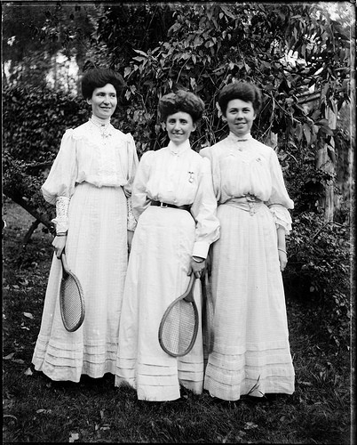 Three young women in light dresses holding tennis racquets