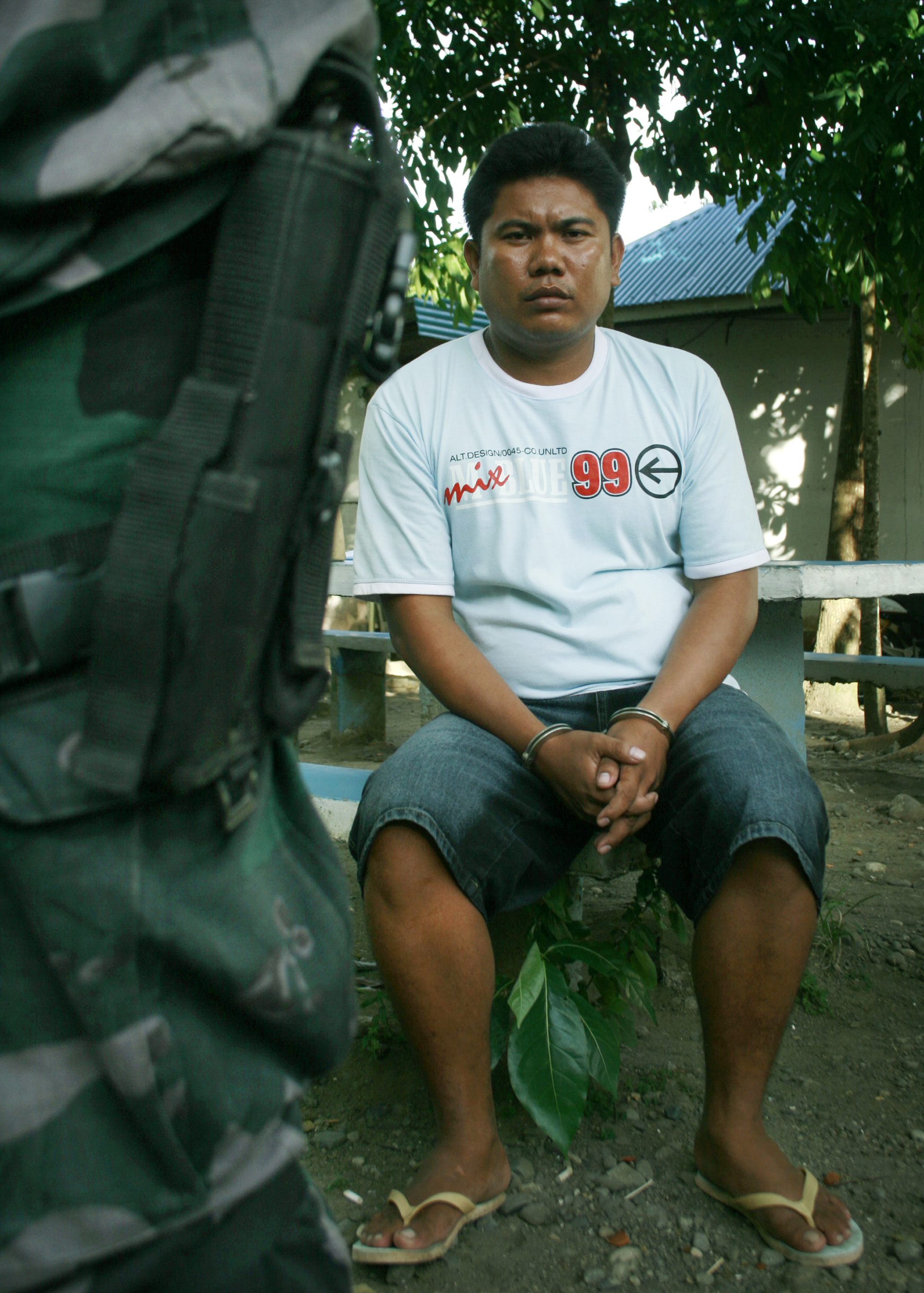 A police officer guards Rammy Moquete, one of Iloilo province's most wanted persons, after he surrendered Monday. (Photo by Tara Yap)