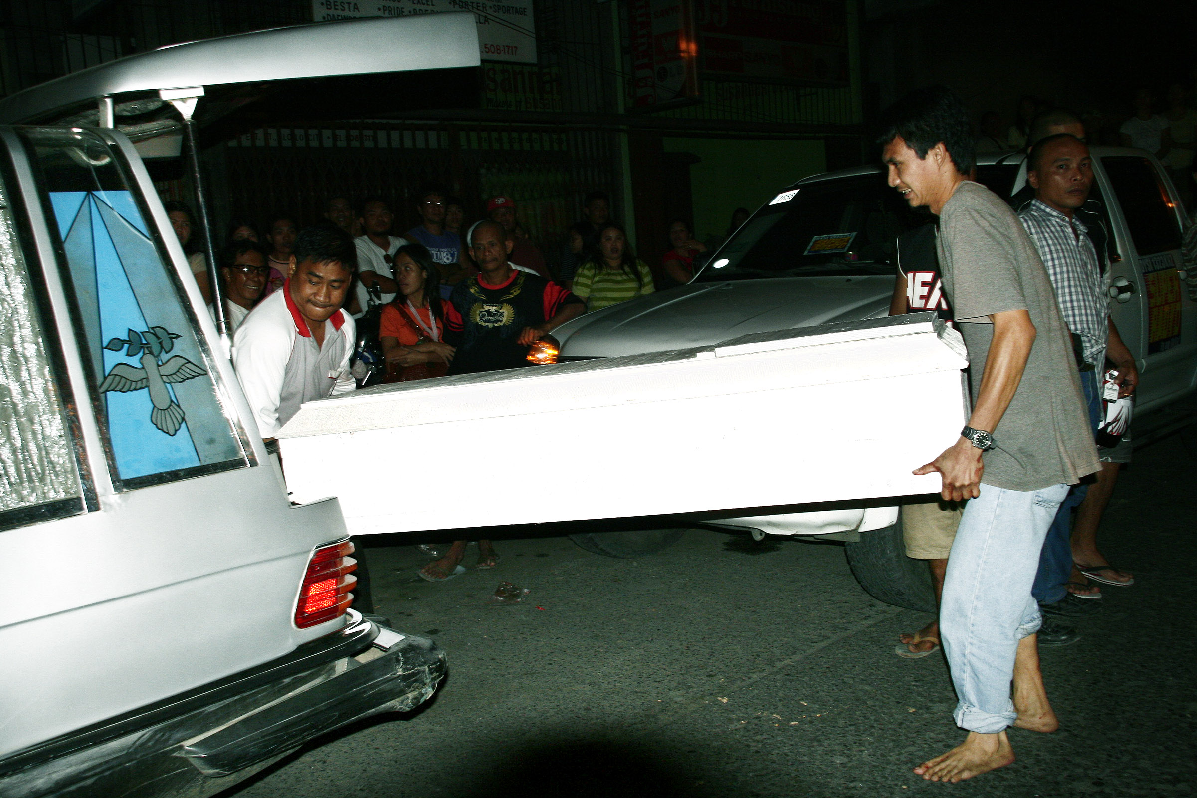 SUICIDE? Workers of a funeral parlor carry a casket containing the body of Julie Fe Balbanida who allegedly took her own life Wednesday inside Uni-Royal Builders Supply in Valeria Street, Iloilo City. (Photo by Tara Yap)
