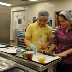 Junior Volunteer Jeanette Lee assists Scott & White Round Rock's Lauren Field in preparing patient meal trays.