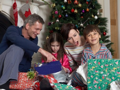 Couple and children opening gifts