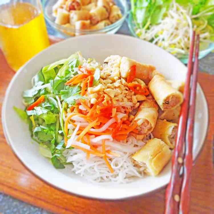 A bowl of bun cha gio, made with vermicelli rice noodles, pickled carrots, fresh herbs and vegetables, spring rolls and nuoc mam.