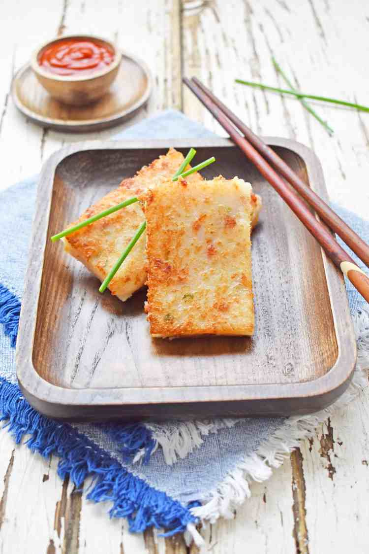 45 degree view of 2 pieces of turnip cake on a wooden plate.