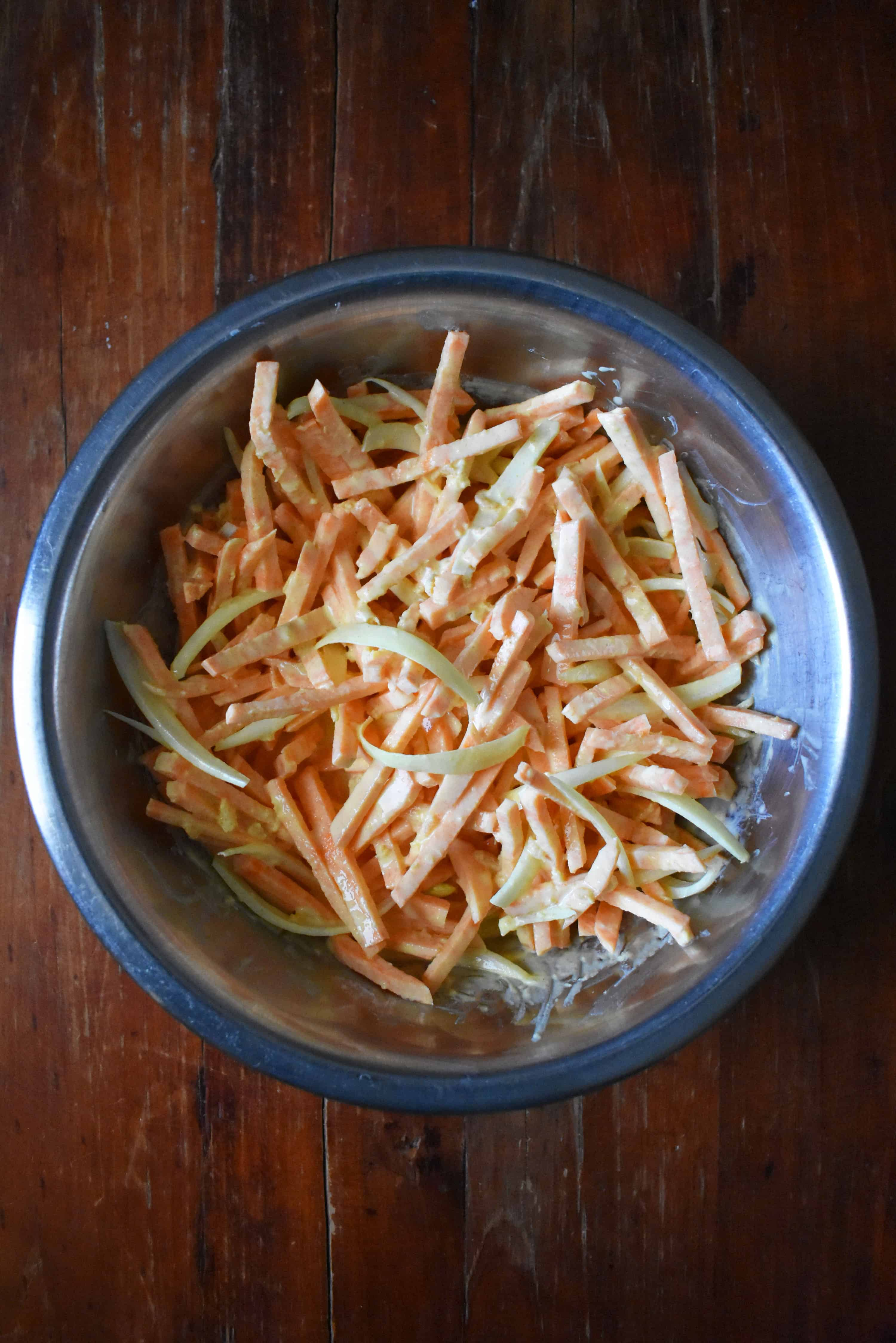A large mixing bowl containing banh tom batter mixture, primarily made up of sweet potato and onion strips.
